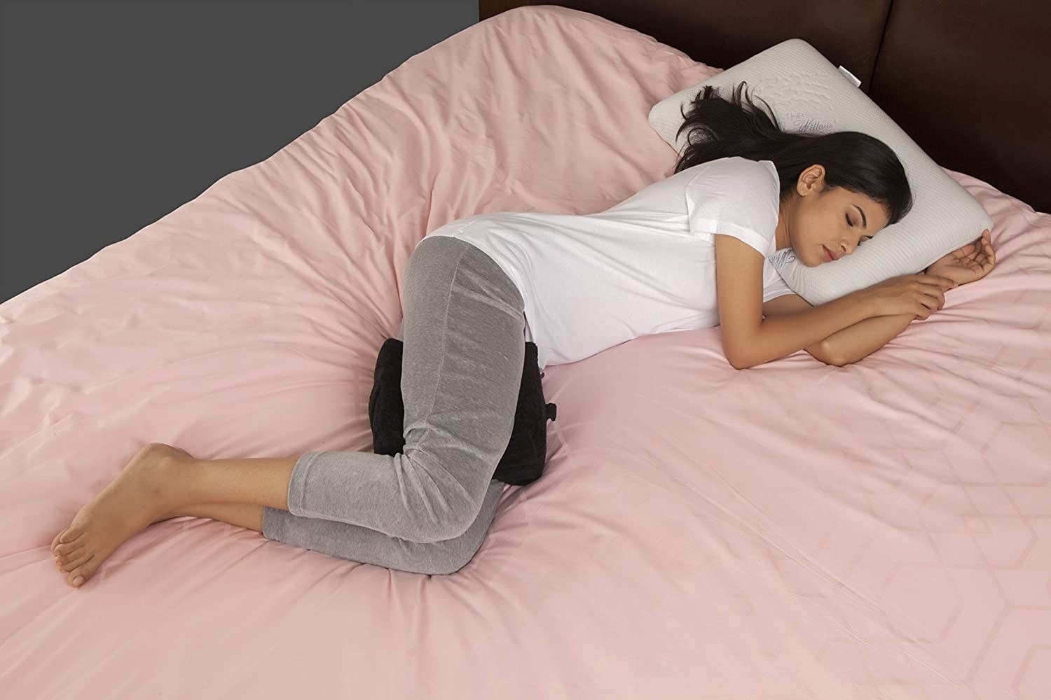 A person sleeping with the pillow between their legs.