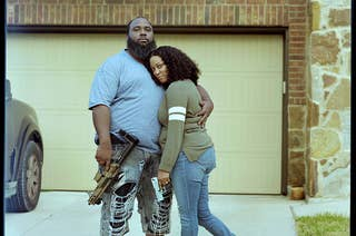 A couple embracing in front of their garage, each is holding a gun which they display for the camera
