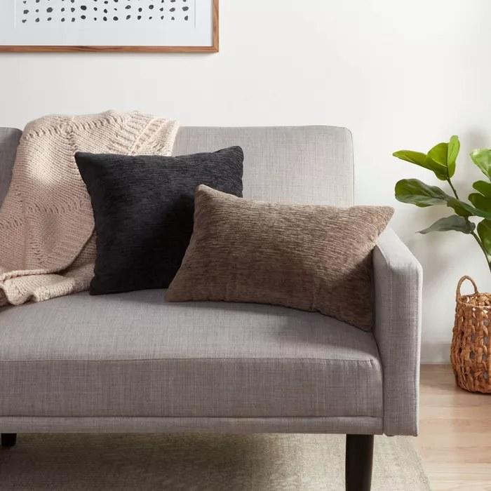 A brown lumbar pillow and a black square pillow