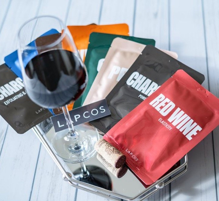 Several of the sheet masks with a glass of wine