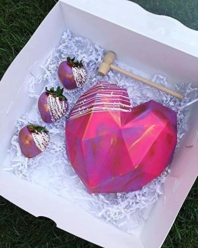 A pink, purple and gold heart-shaped piñata cake with the hammer and a few strawberries on the side.