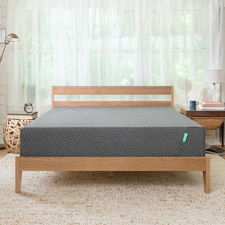 A gray mattress on a bed frame