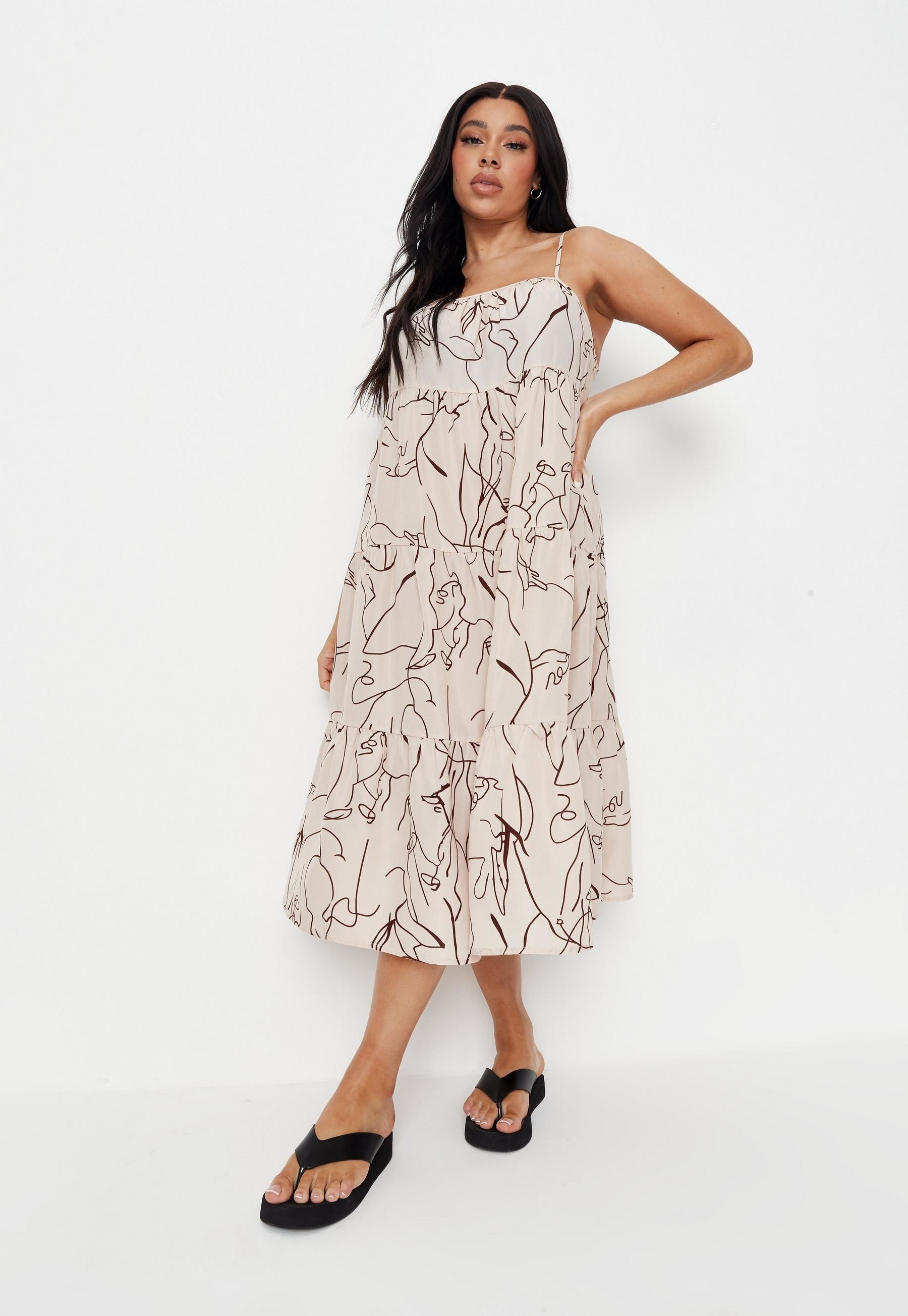 model wearing spaghetti strap tiered maxi in beige with dark brown line pattern on it