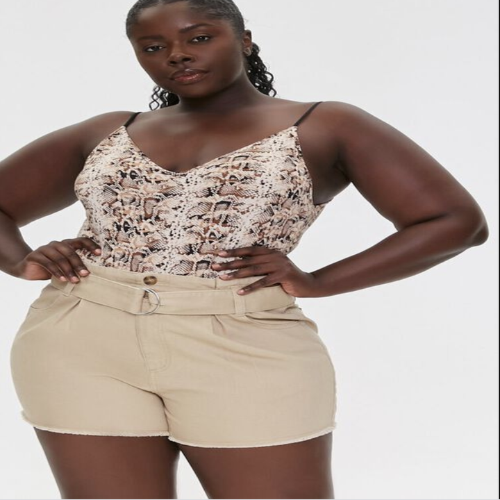 Model in a pair of high waisted khaki shorts with a loop buckle belt