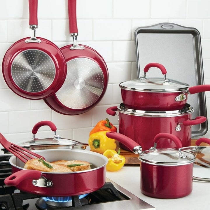 A red cookware set with pots, pans, and lids