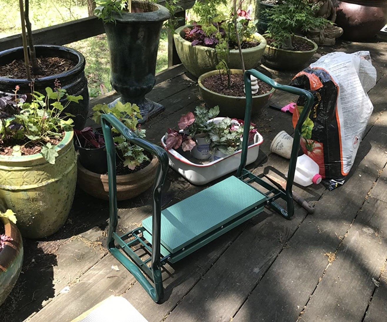 a kneeler bench for gardening next to potted plants