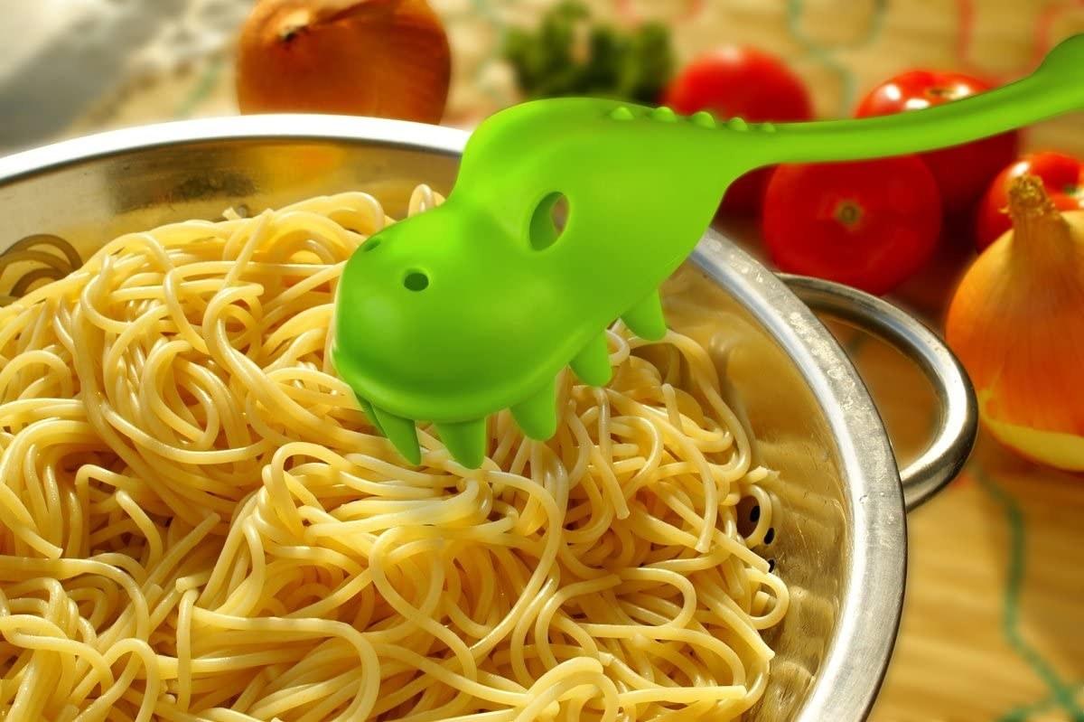 Dinosaur-shaped pasta server sitting over bowl of pasta