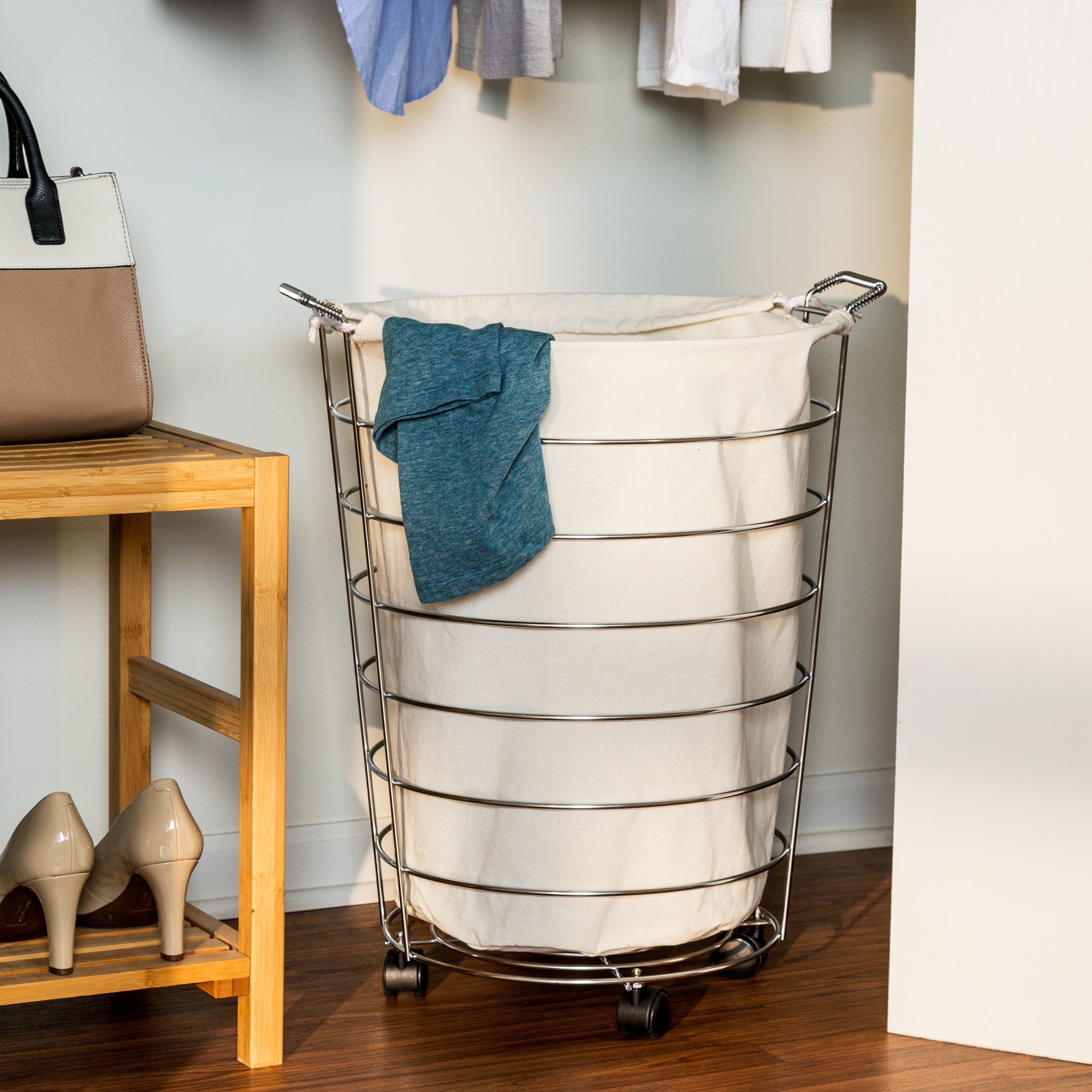 stainless steel hamper on wheels with a white laundry bag inside of it