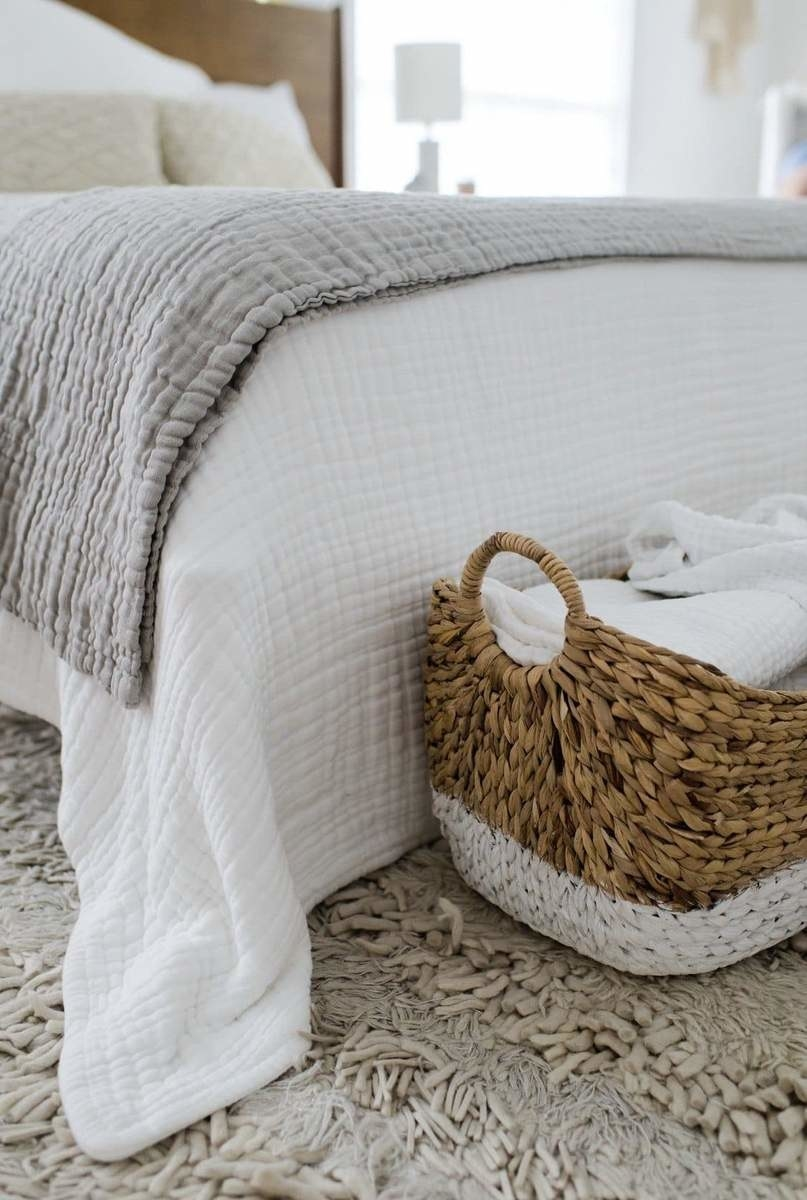 a grey throw and white throw on a bed