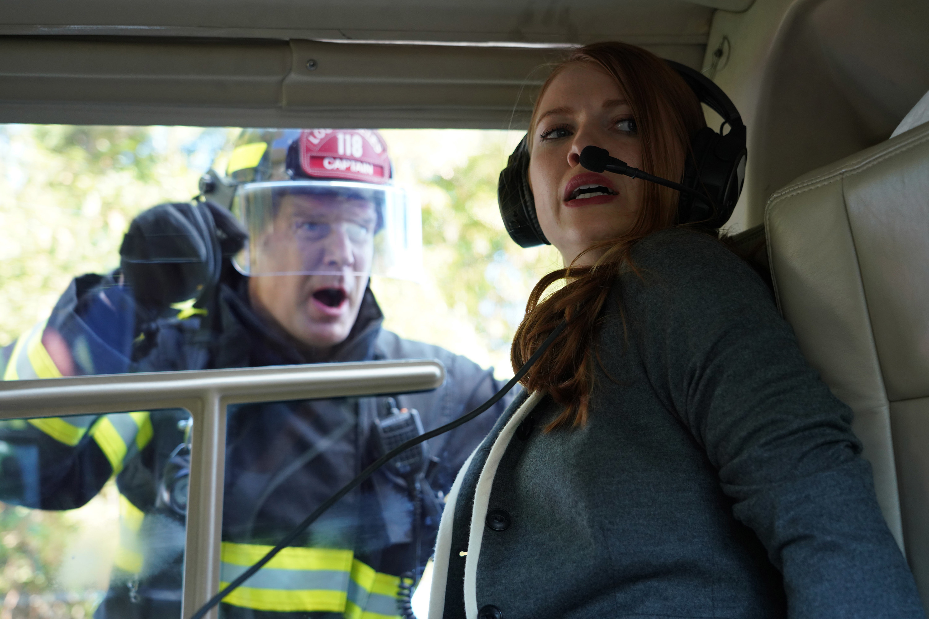 A firefighter speaks to a woman trapped in a helicopter