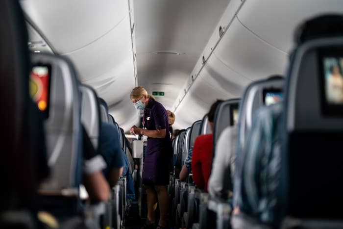 A flight attendant in a mask walks down an aisle on an airplane