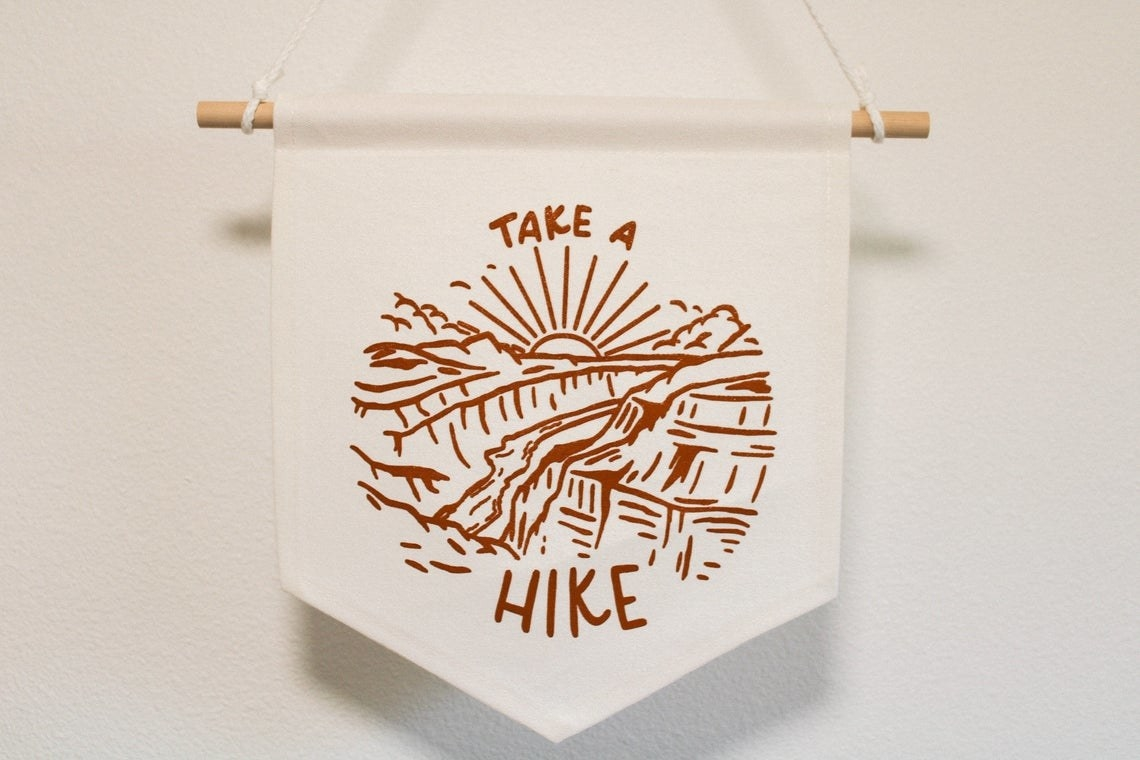 Small banner that says Take A Hike with illustration of the Grand Canyon