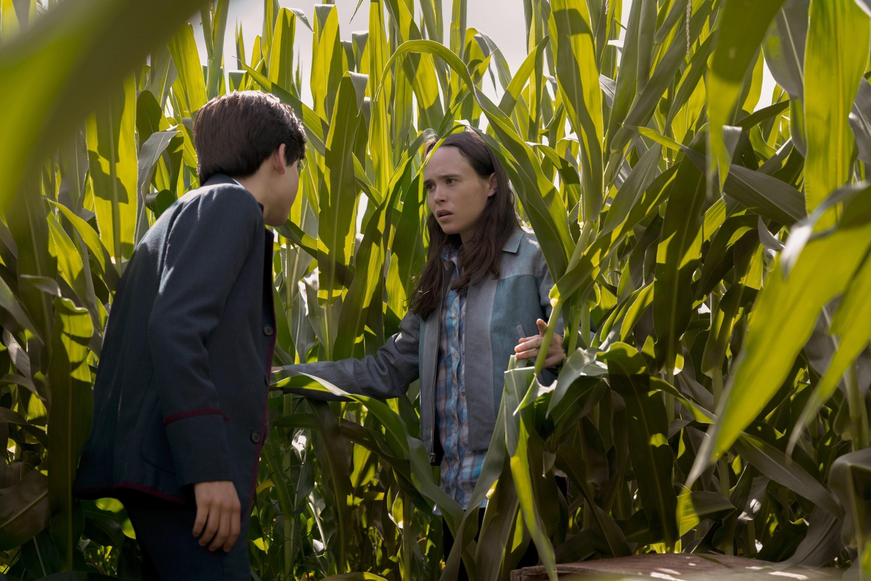 Aidan Gallagher and Ellen Page speaking in a corn field