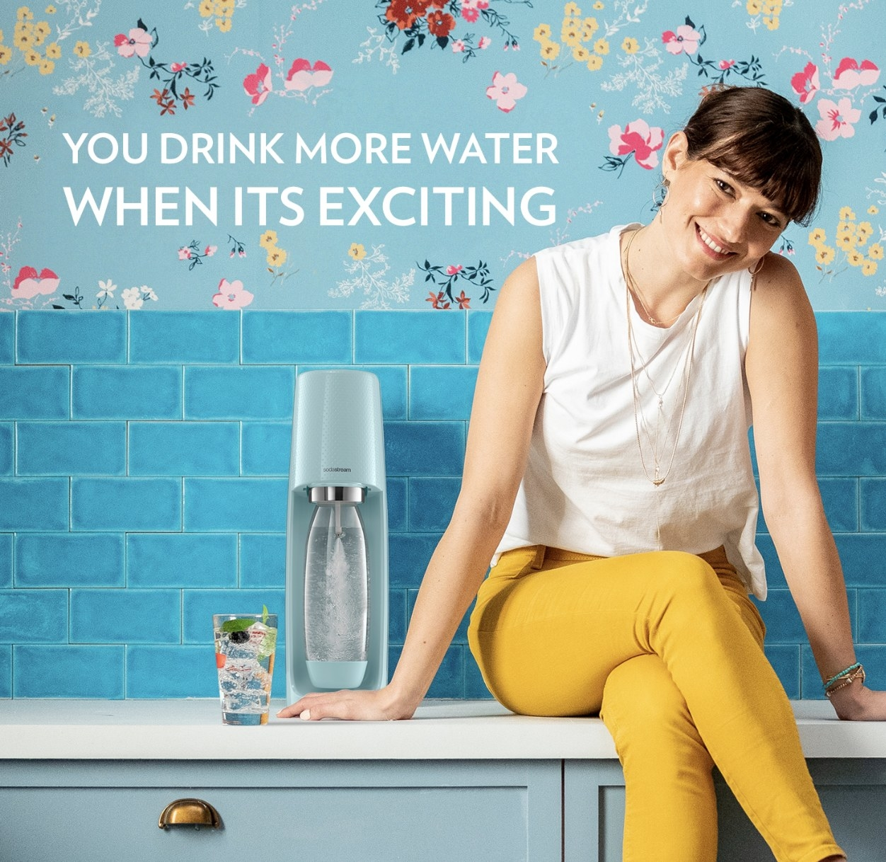 A person sitting next to a SodaStream