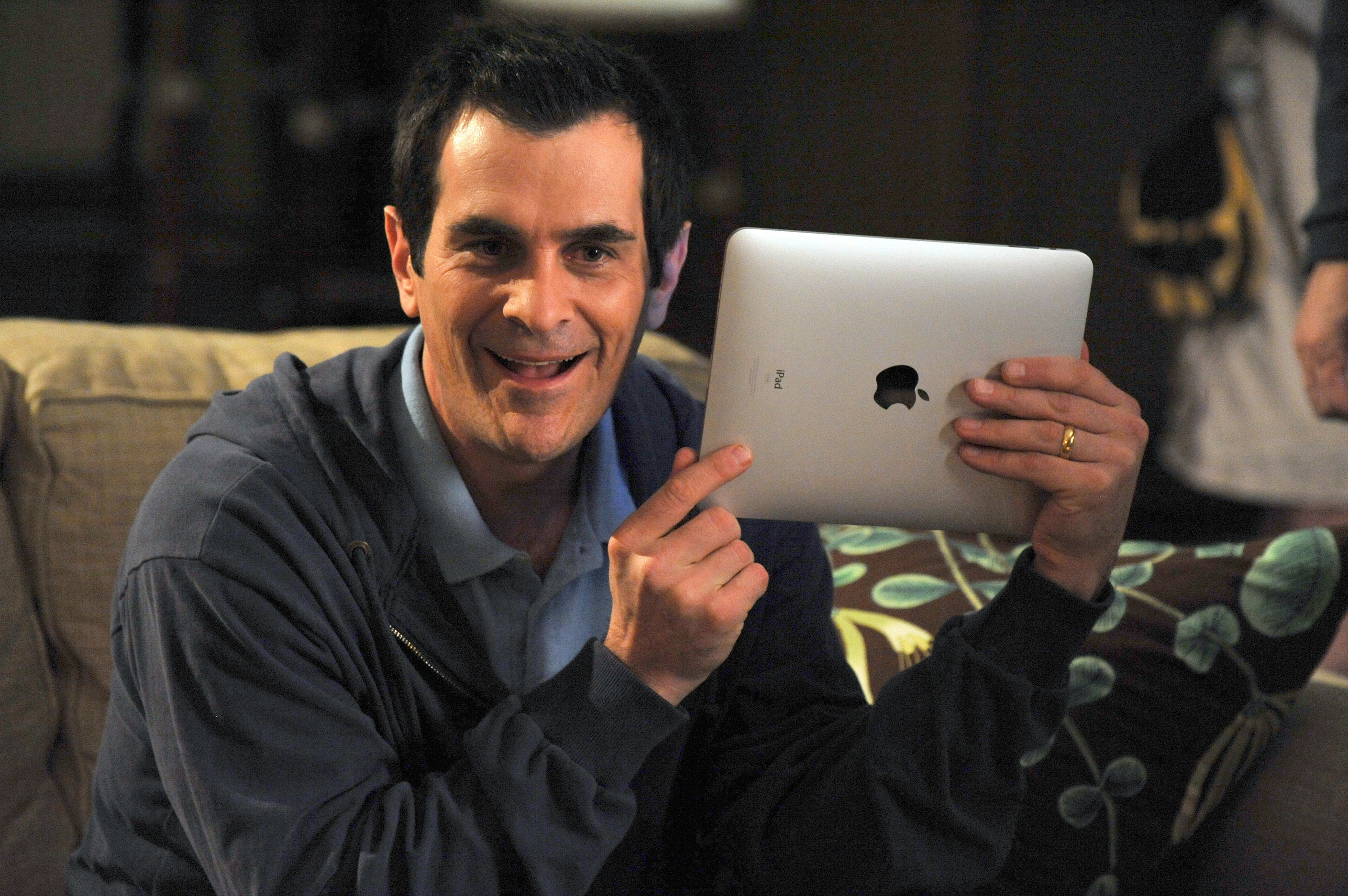 Ty Burrell holding an iPad with excitement