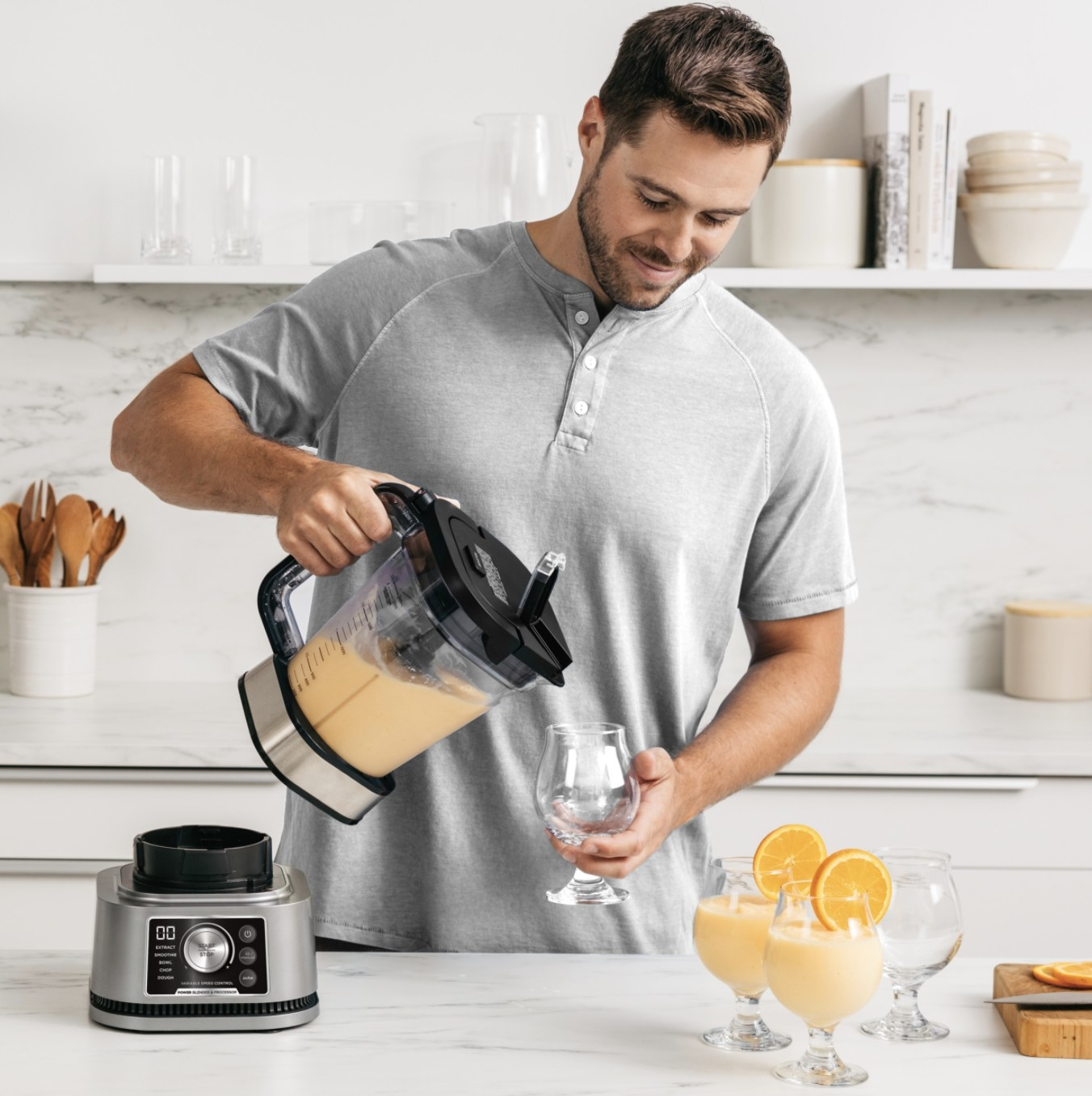 A person pouring a smoothie into a cup from a blender