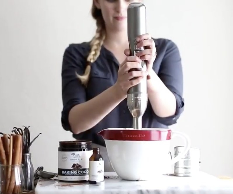 A person using the hand mixer in a bowl