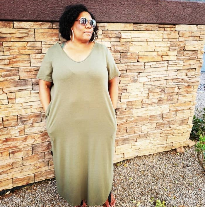 A reviewer wearing the dress in green