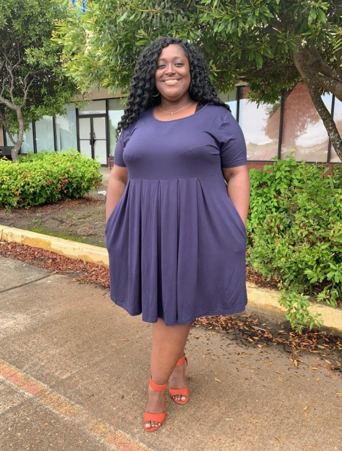 A reviewer wearing the dress in navy blue