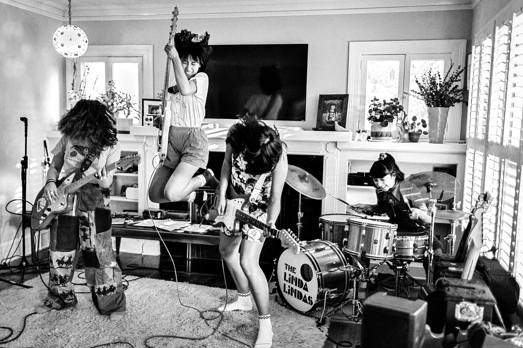 Four young girls jam out in a suburban living room, two playing guitar, one playing guitar and jumping into the air, and one on drums