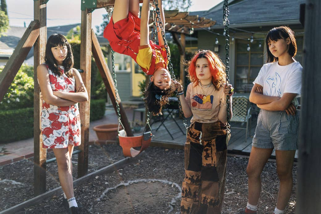 The four girls at a swing set in a suburban backyard, one hanging upside down