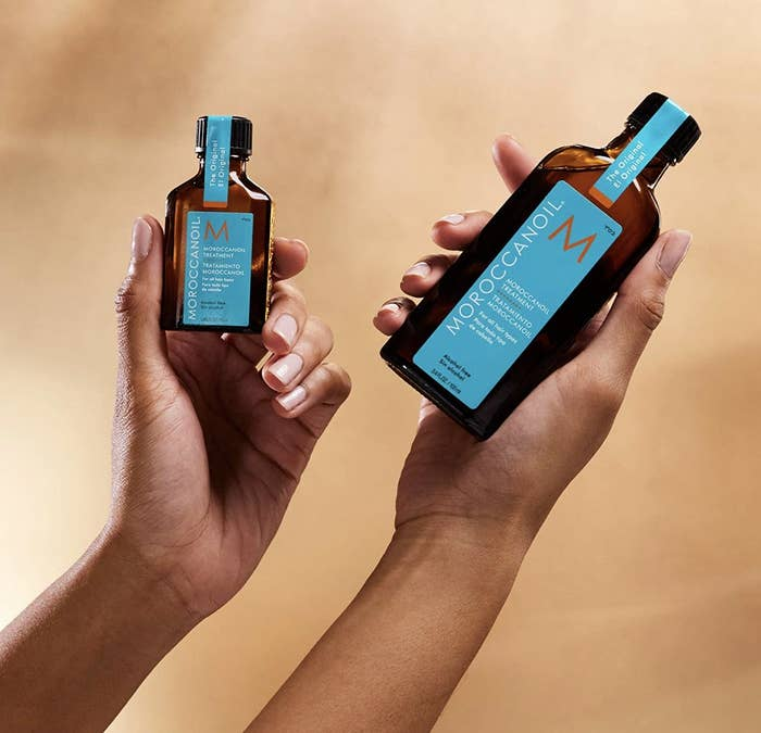 A woman holding two bottles of hair oil