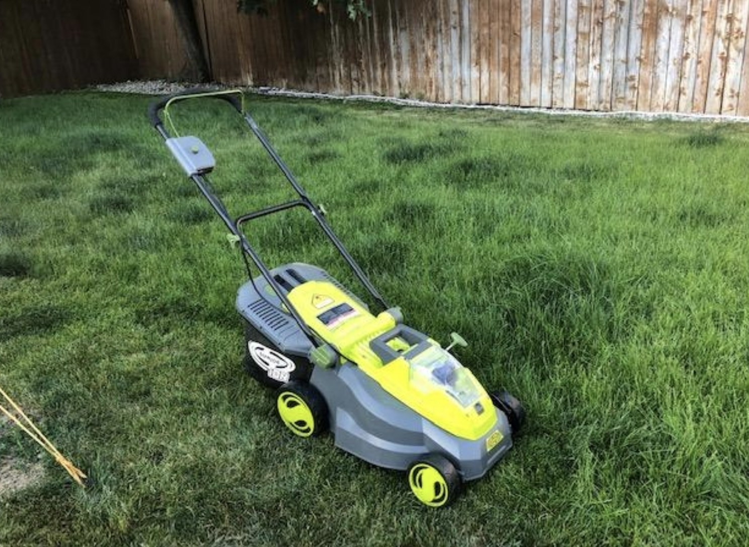 a lawn mower in the middle of a yard on top of freshly cut grass
