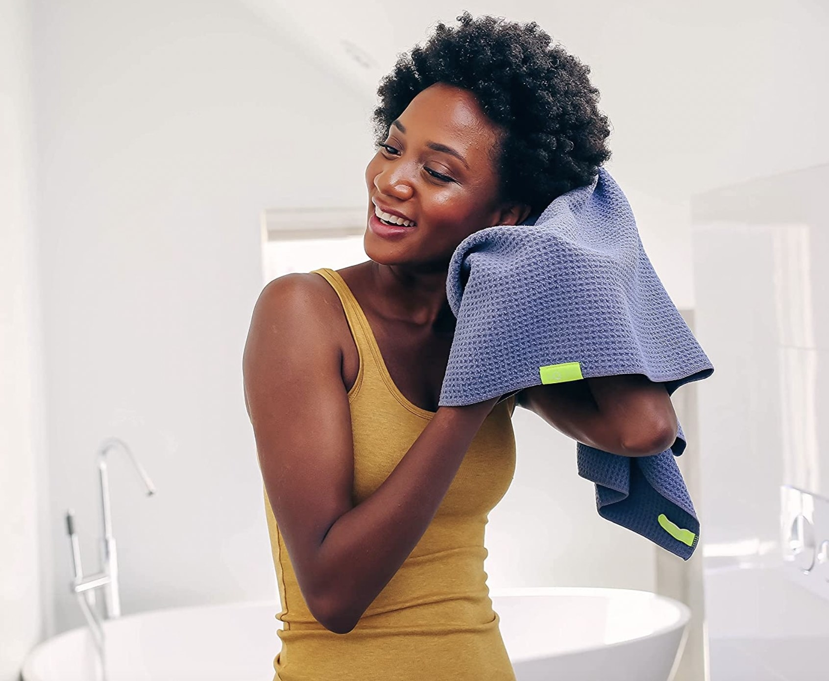 A woman drying her hair with a towel