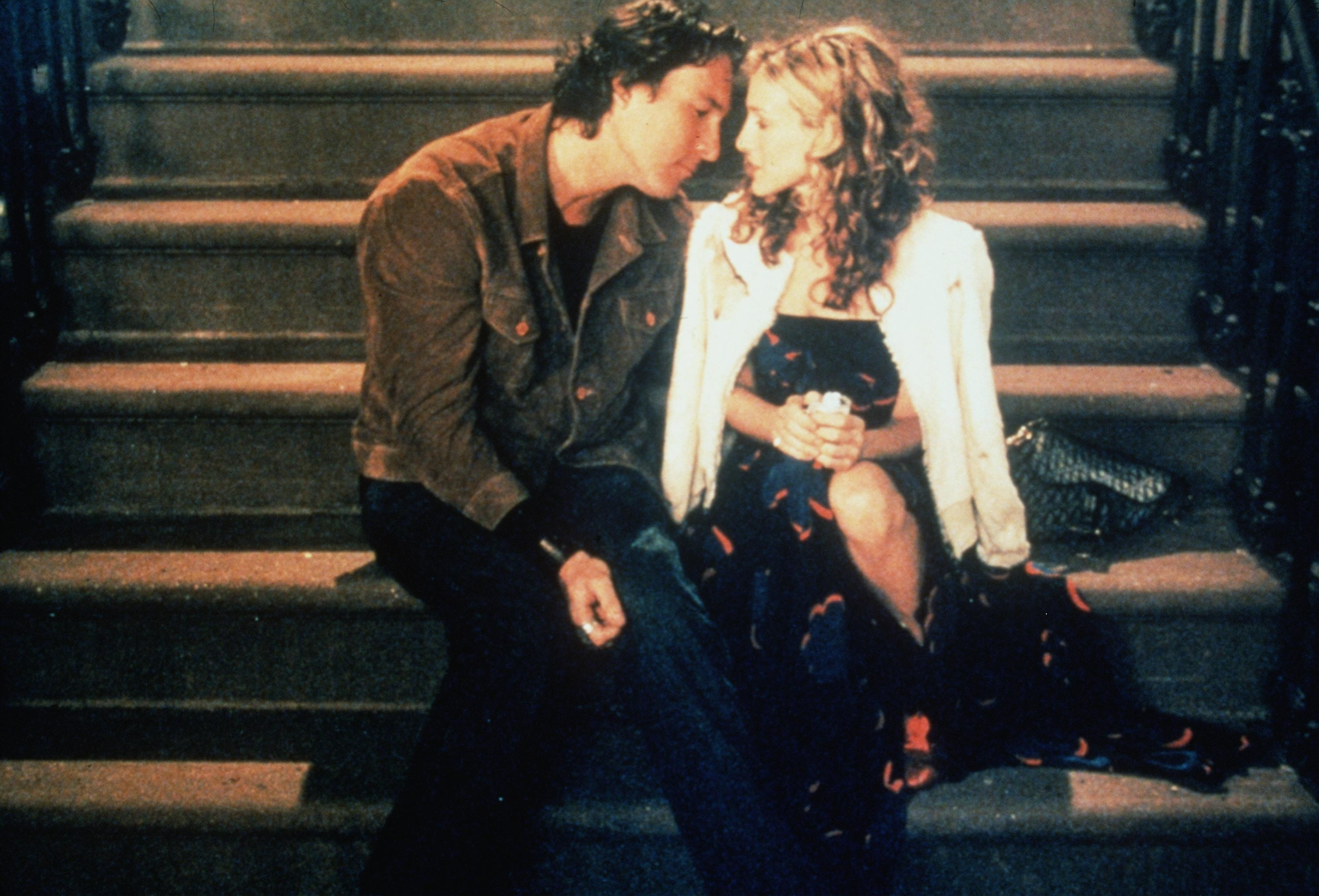 Carrie and Aidan sit on the steps outside a building