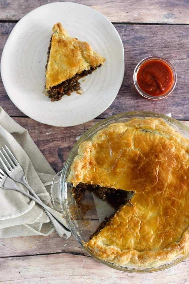 Mince-and-cheese pie with a single slice placed on a plate next to pie plate.