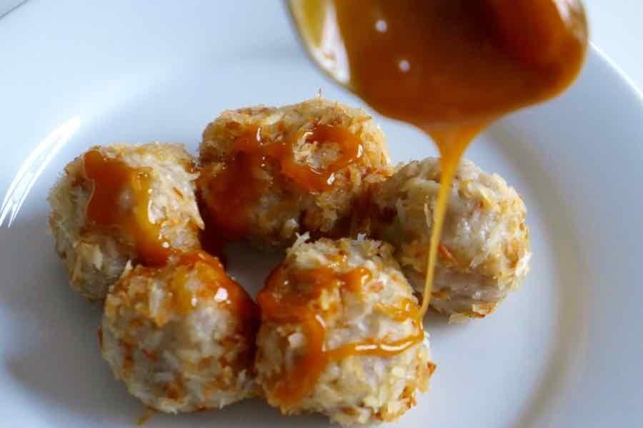 Spoon drizzling coconut caramel on top of five sweet coconut dumplings.