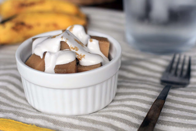 Small bowl filled with cubes of Banana Po'e dessert, drizzled with banana cream