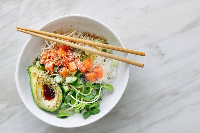 Bowl with poke, rice, and half of an avocado filled with soy sauce, with pair of chopsticks perched on top.