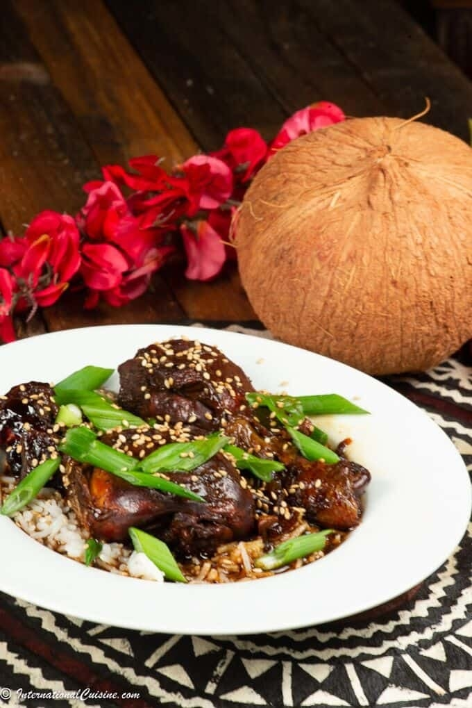 Plate with Samoan chicken on bed of coconut rice, all sprinkled with sesame seeds. A large coconut is placed next to plate