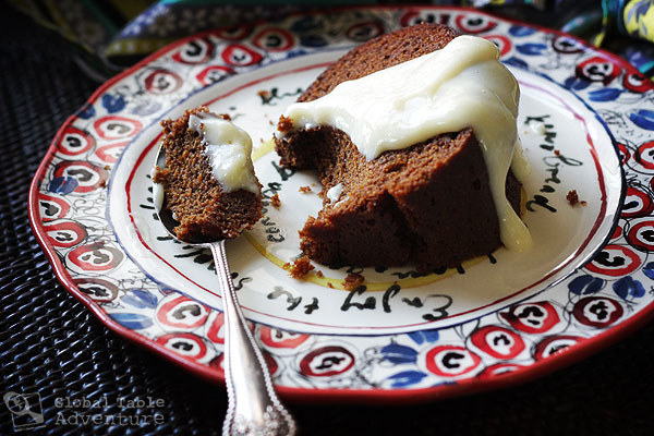 Large slice of Samoan spice cake, with a spoon that's taken a big chunk out of it hanging out on the plate. The cake is drizzled with thick sweet custard