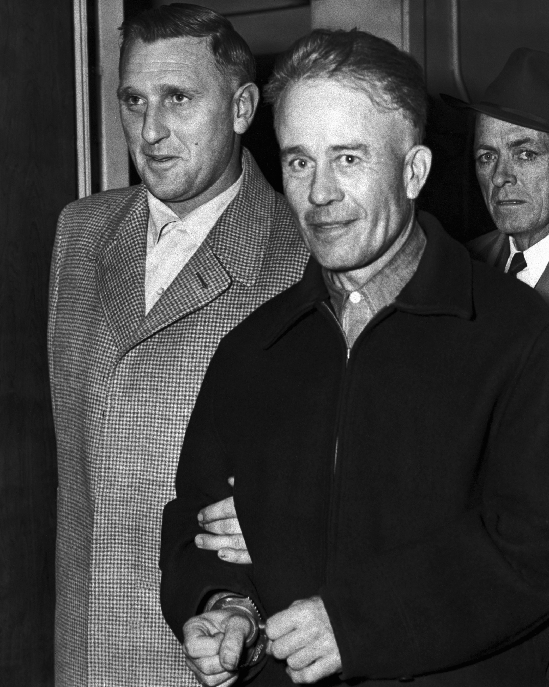 Ed Gein with a creepy smile on his face as he's being escorted by police in handcuffs