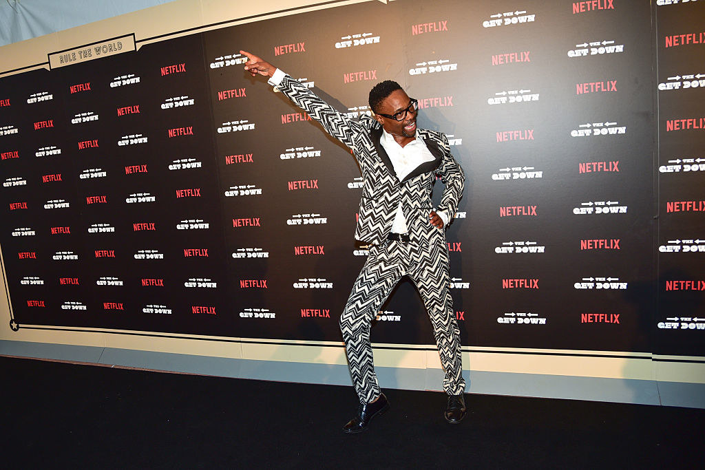 Billy Porter strikes a disco pose while wearing a black and white patterned suit.