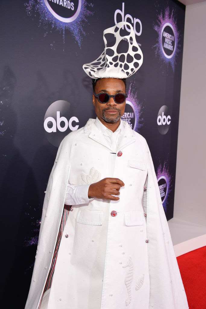 Billy Porter wears an all white suit dress with a matching sculpture hat.