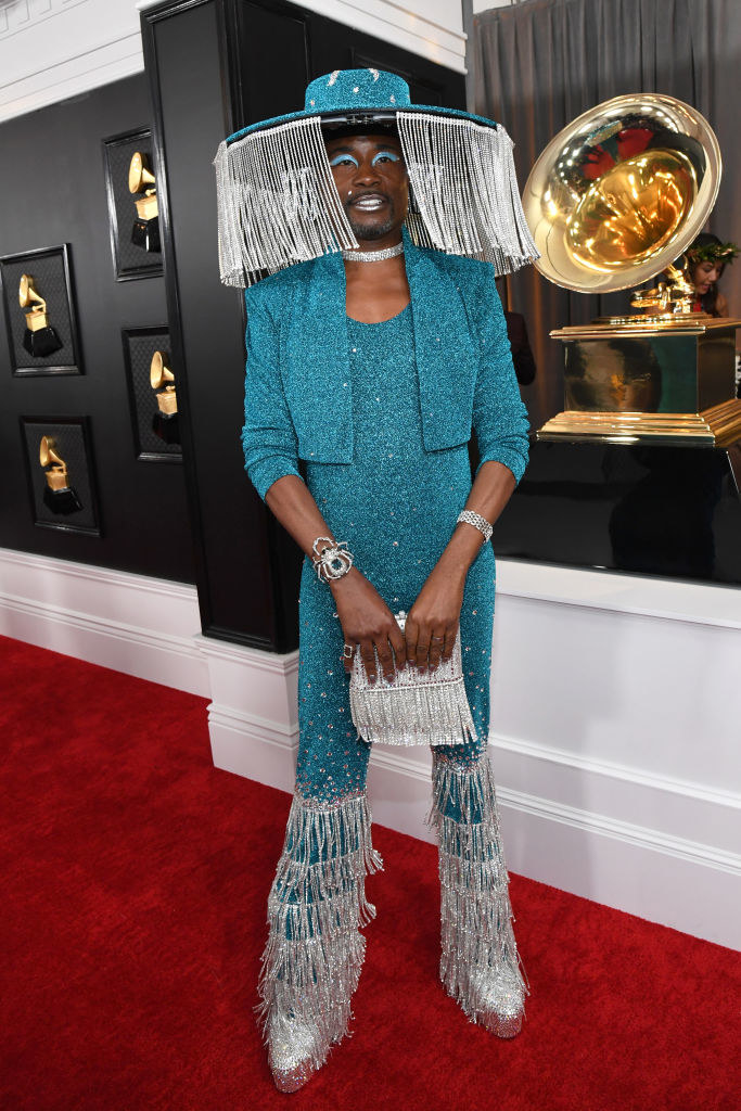 Billy Porter wears a sparkly blue jumpsuit with tassel boots and a wide brim hat with tassels hanging off it.