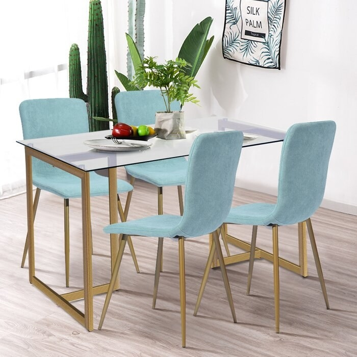 four mint chairs with gold legs and a glass table with gold legs