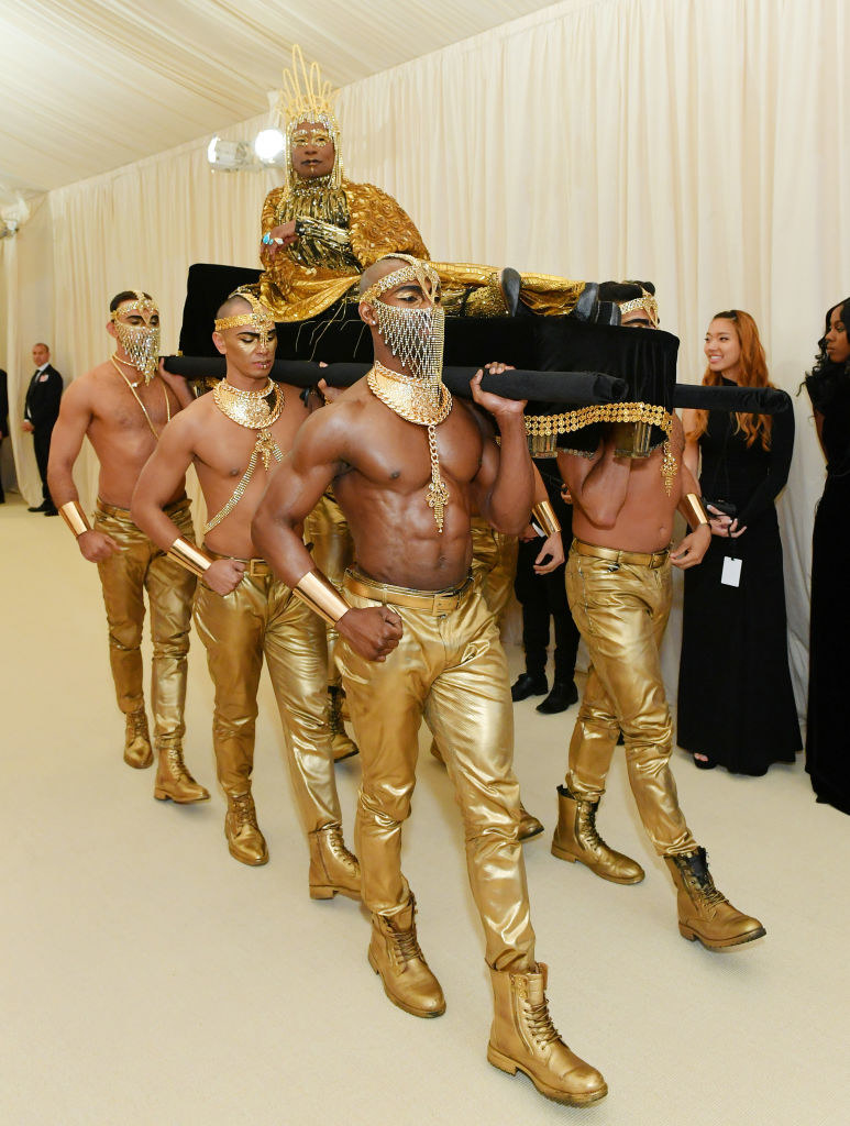 Billy Porter wears a golden angel costume while laying on a long black couch being carried by shirtless men.