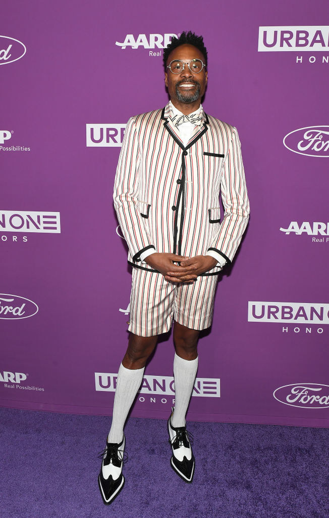 Billy Porter wears a pinstripe blazer and matching knee length shorts, knee length socks, and black and white dress shoes.