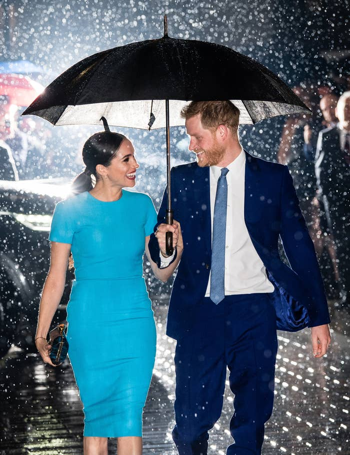 meghan markle and prince harry walking under an umbrella together