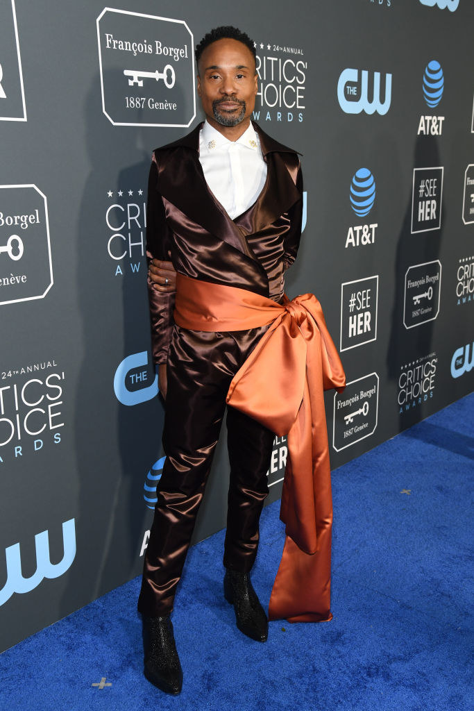 Billy Porter wears a brown suede suit with an orange ribbon tied into a bow as a belt.