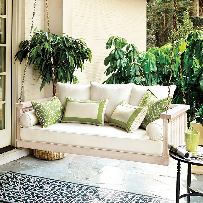A hanging wooden bench swing with ivory cushioned bottom and pillows on a porch