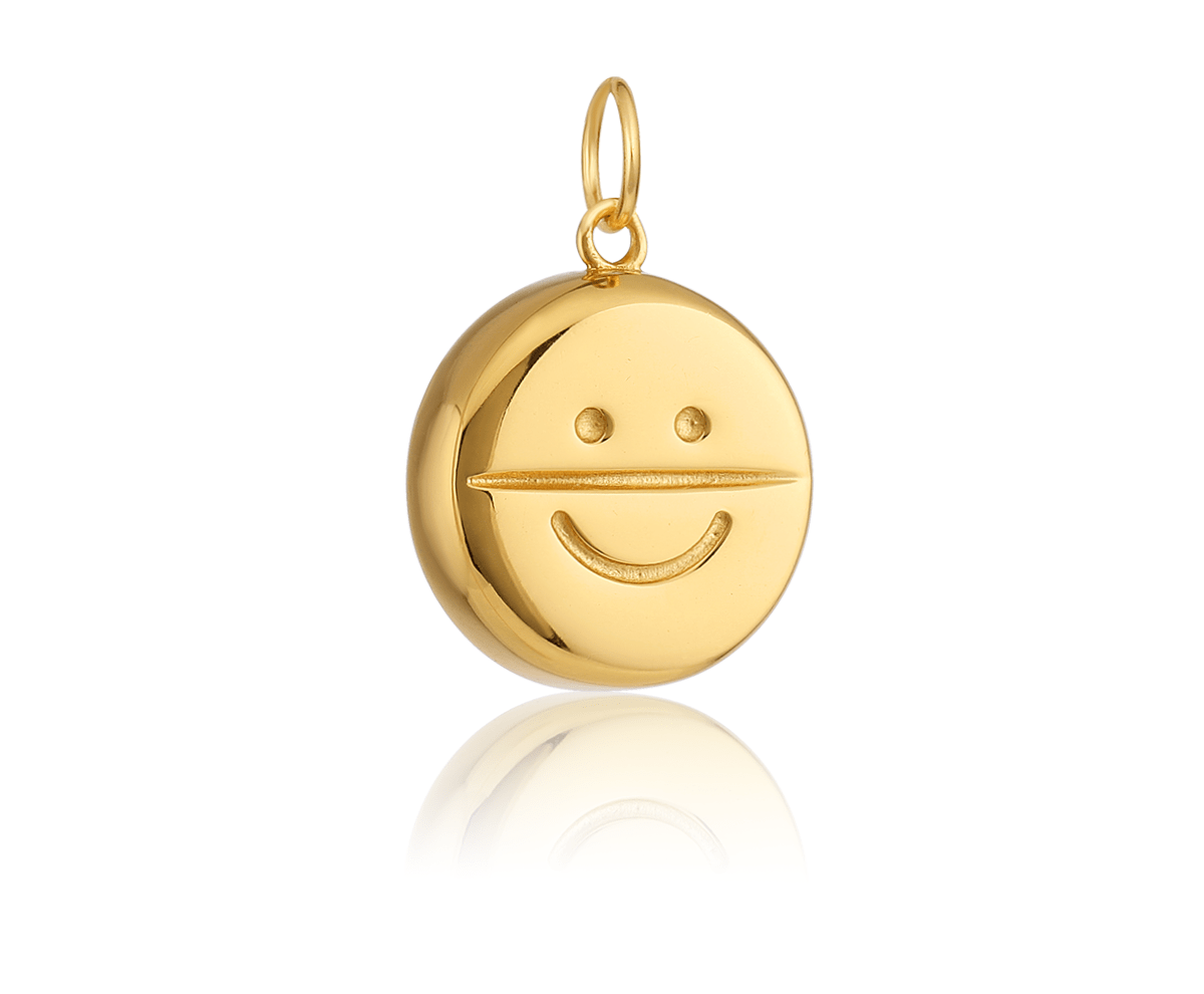 a gold pill-shaped charm with a smiley face on it