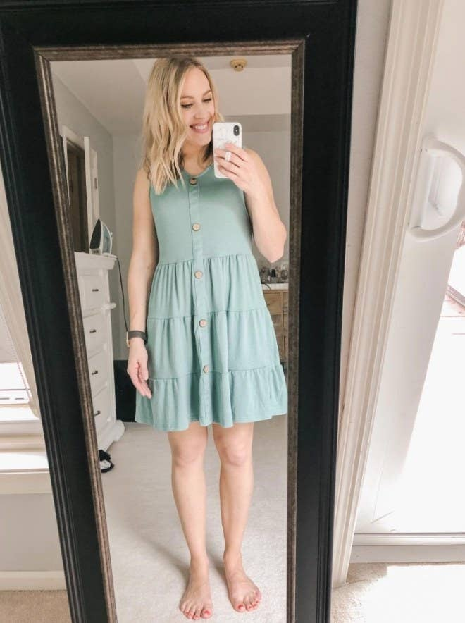 A reviewer wearing the light green tiered, sleeveless, v-neck, button-down mini dress