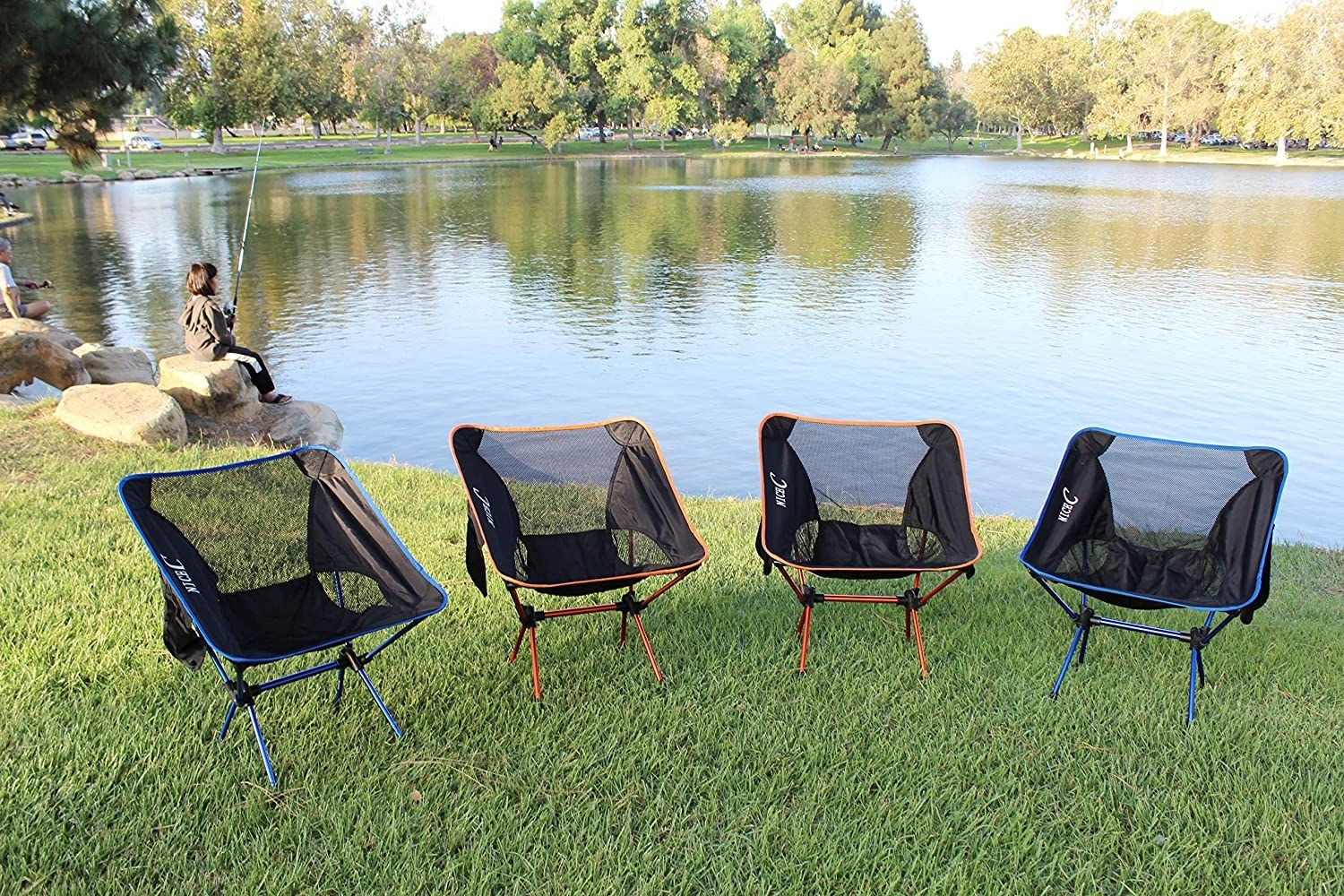 A row of four portable camping chairs by a lake