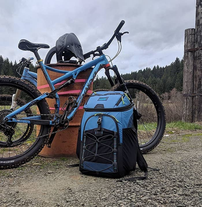 The cooler backpack next to a mountain bike on a trail