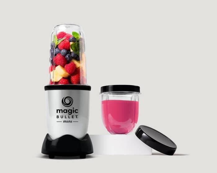 product image of the blender full of fruit, with blender mug full of pink smoothie to the right